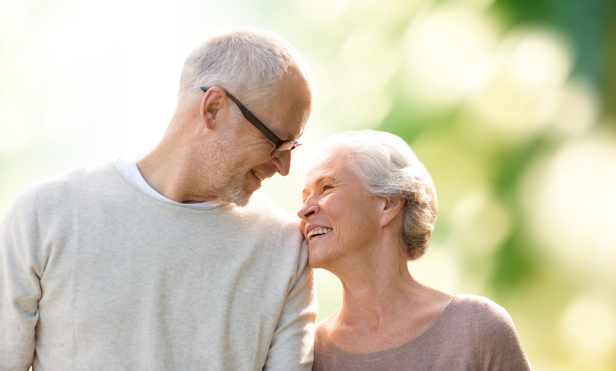 family, age, love, relations and people concept - happy senior couple over green natural background